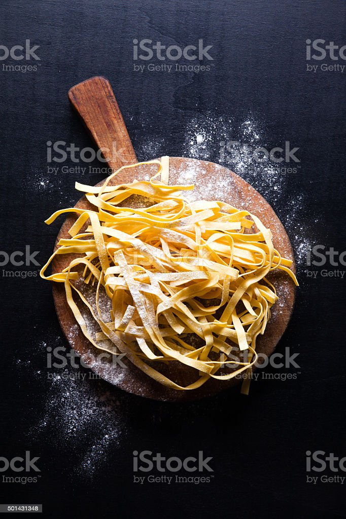 fresh pasta on vintage cutting board stock photo