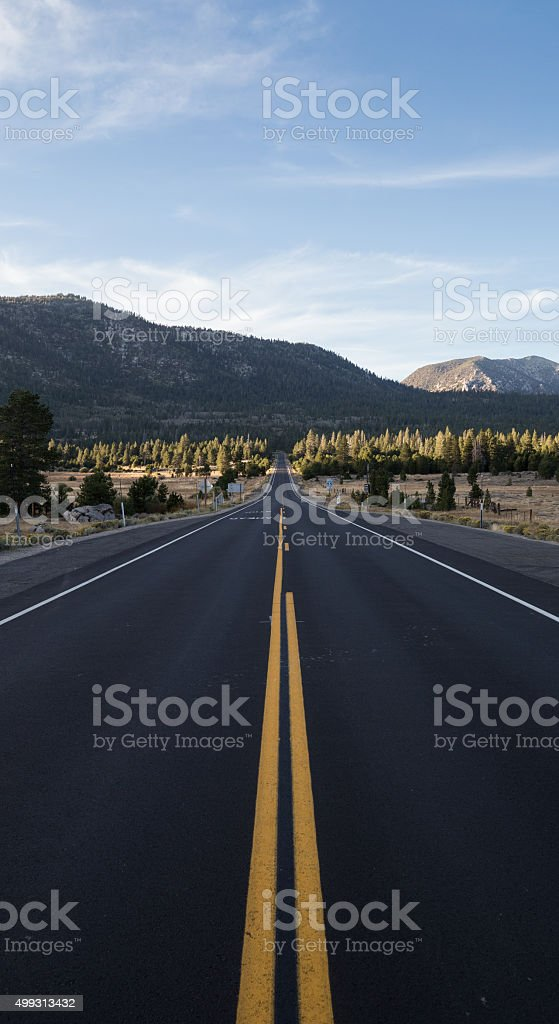 Fresh paved straight stretch of mountain road stock photo