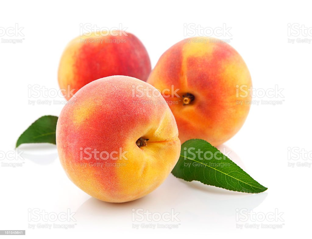 Fresh peaches and green leaves on white background royalty-free stock photo