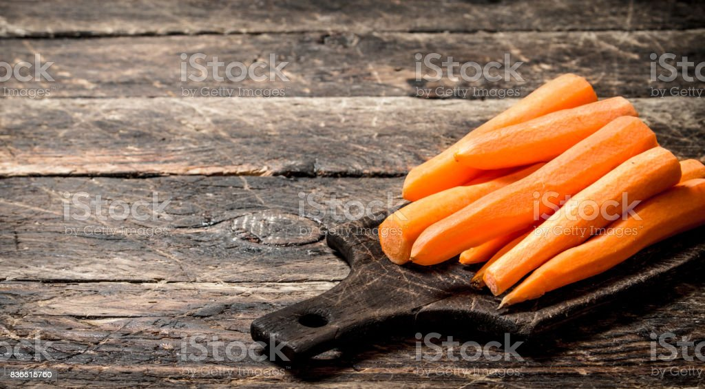 Fresh peeled carrots on a cutting Board. On the old wooden table. stock photo