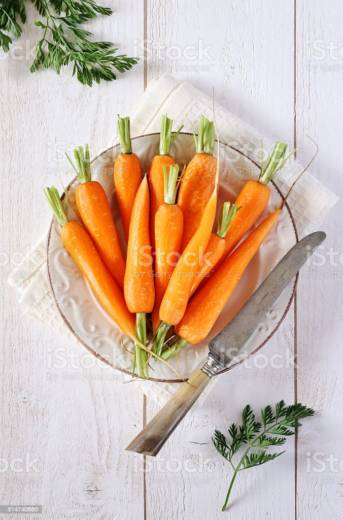 Fresh peeled carrots on green tops stock photo