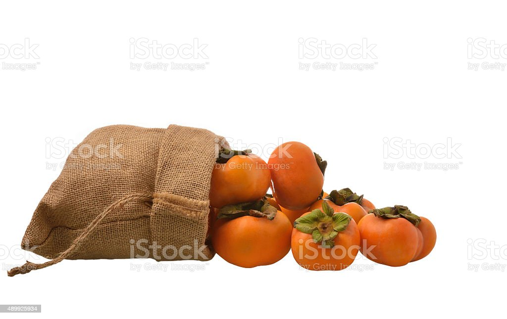 Fresh persimmon in the sack on white background. stock photo