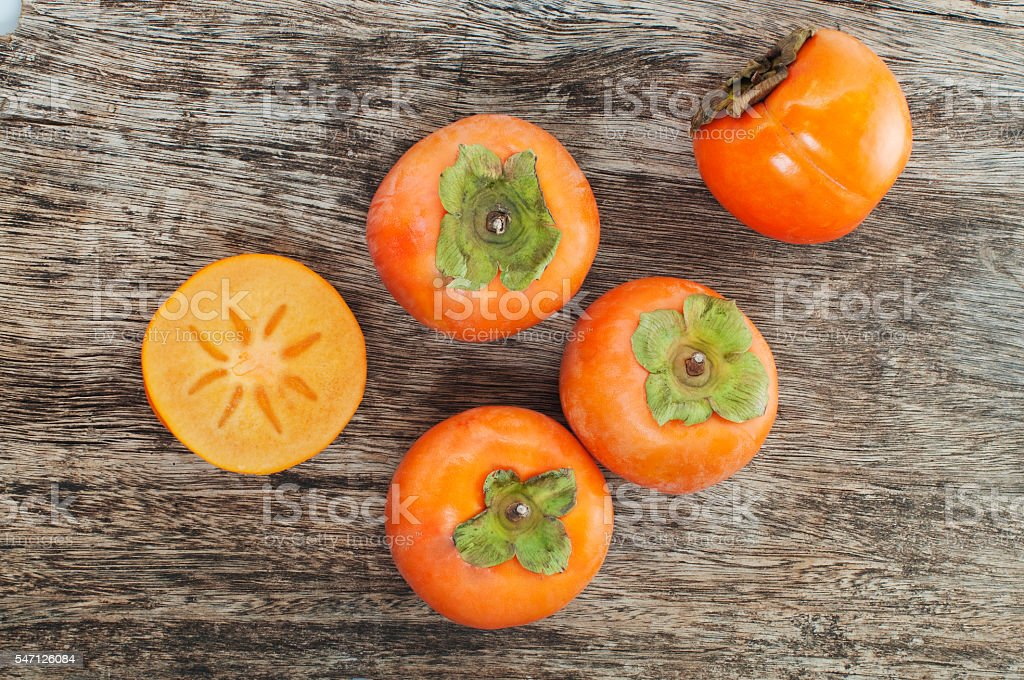 fresh persimmons on a wooden table stock photo