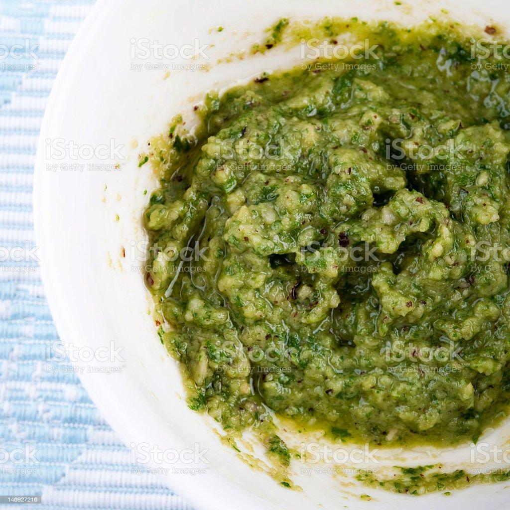 Fresh pesto sauce in white bowl stock photo
