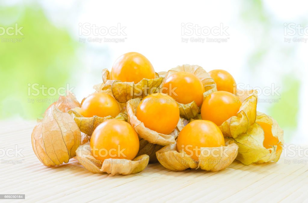 Fresh pichuberry (Cape Gooseberry), very delicious and healthy berry fruit, uchuva on bamboo mat with nature light green bokeh background stock photo