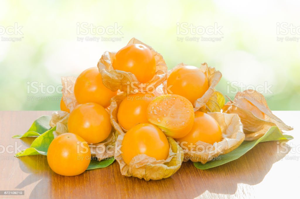Fresh pichuberry (Cape Gooseberry), very delicious and healthy berry fruit, uchuva on brown wooden table and leaves with nature light green bokeh background in the garden stock photo