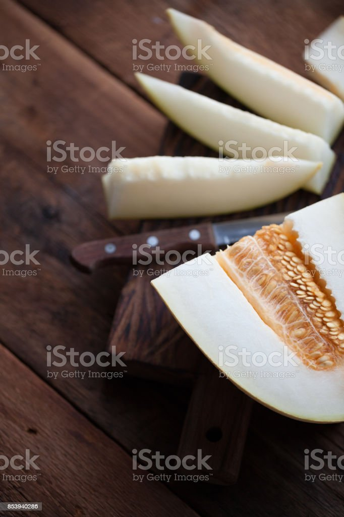 Fresh pieces of melon on the wooden background stock photo