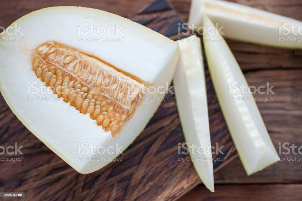 Fresh pieces of melon on the wooden background. top view stock photo