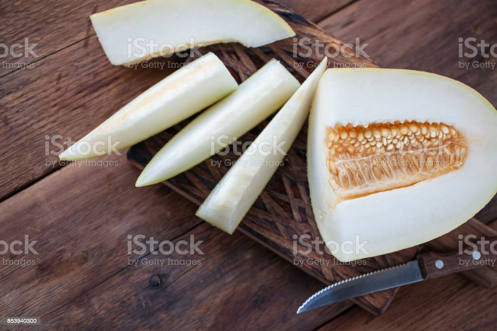 Fresh pieces of melon on the wooden background. top view with copy space stock photo
