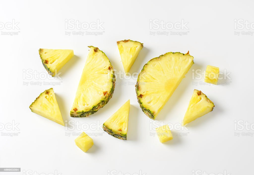 Fresh pineapple slices and wedges stock photo