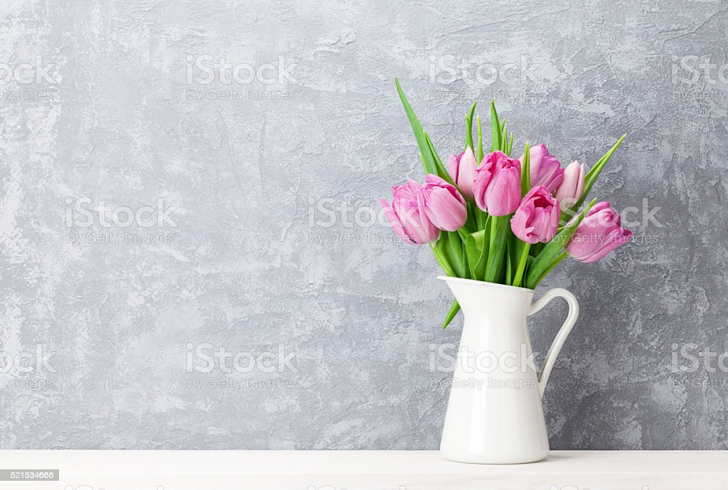 Fresh pink tulip flowers bouquet on shelf in front of stone wall....