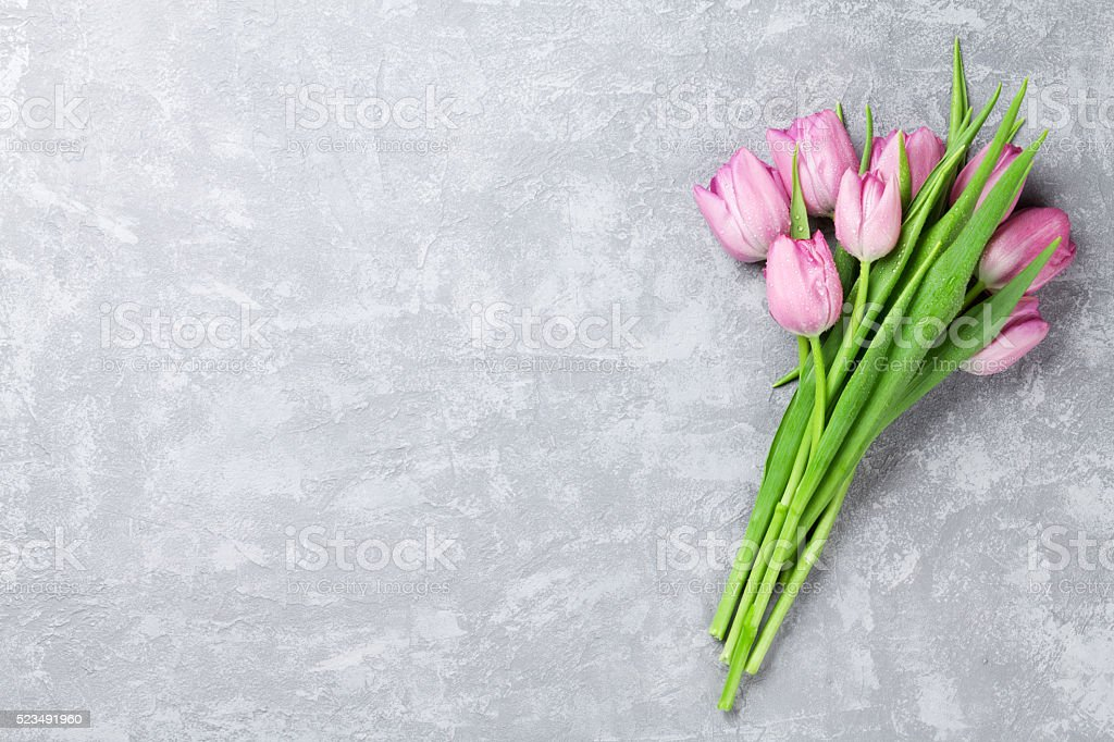 Fresh pink tulip flowers on stone table stock photo