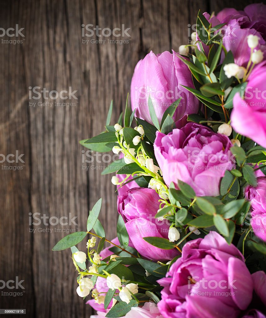 fresh pink tulips and lily of the valley on wood stock photo