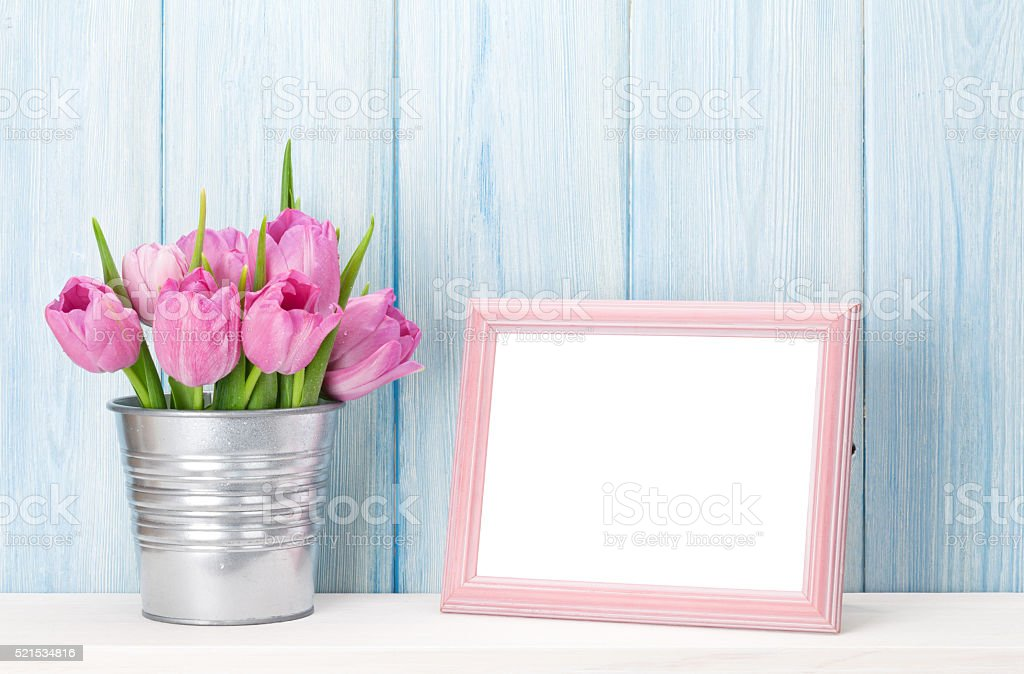 Fresh pink tulips bouquet and photo frame stock photo