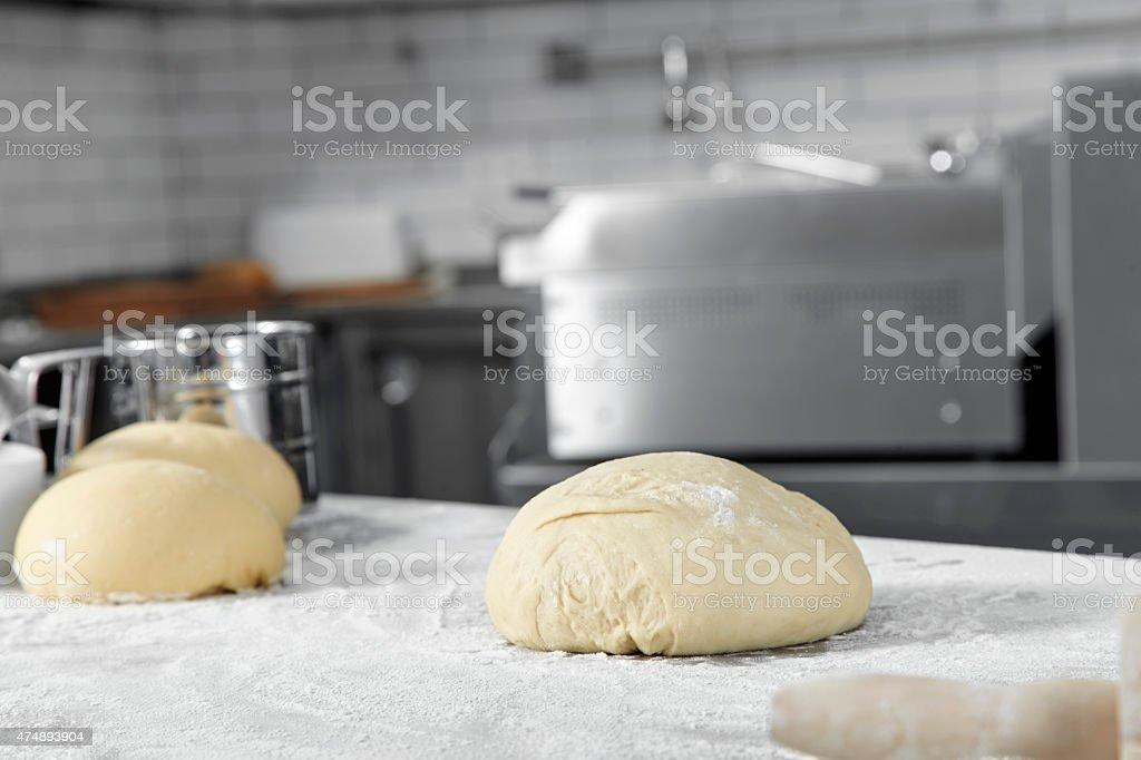 Fresh pizza dough rolled into four round balls stock photo