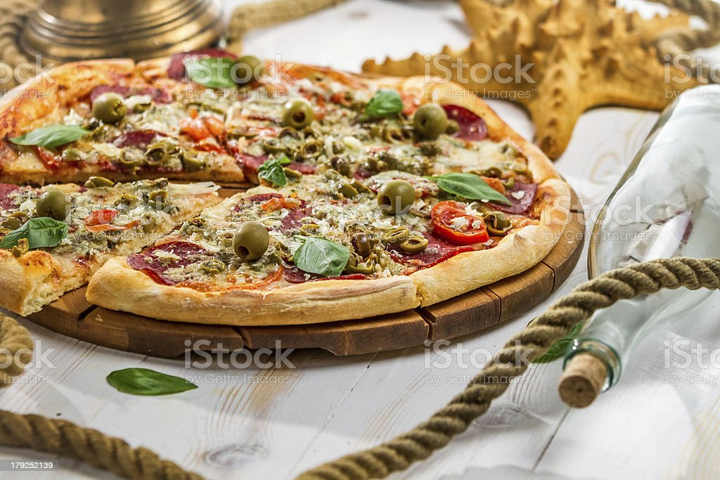 Fresh pizza on a boat made of salami and olives royalty-free stock photo