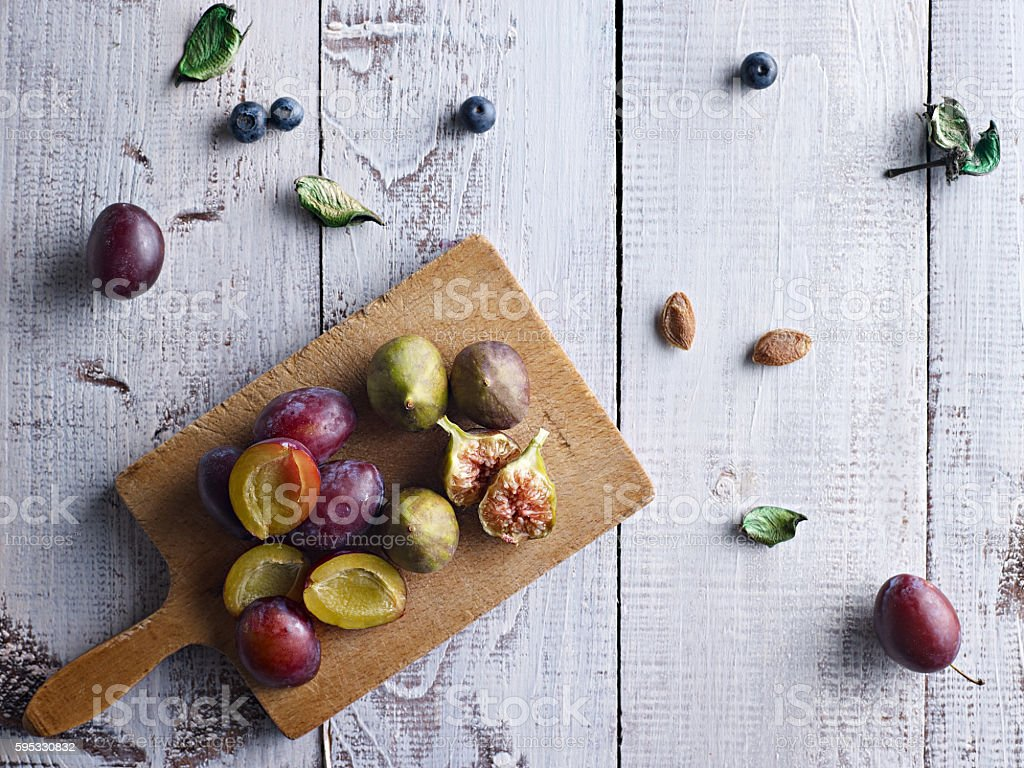Fresh plums and figs on a wooden background. stock photo