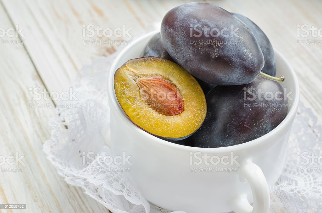 Fresh plums in white bowl on light background stock photo