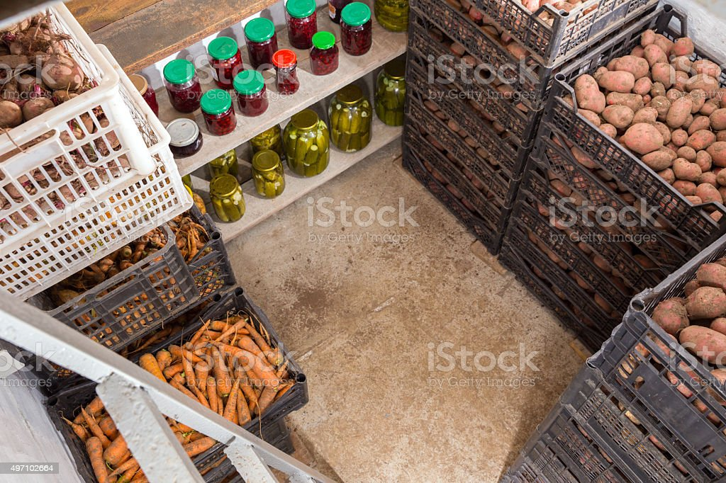 Fresh potatoes, carrots and canned vegetables in the cellar stock photo