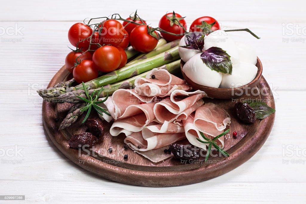 Fresh prosciutto with basil and mozzarella stock photo
