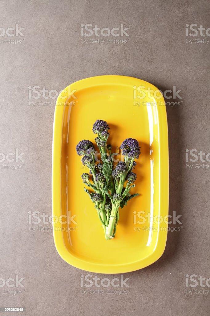 Fresh purple broccoli on a yellow plate. Dark background. stock photo