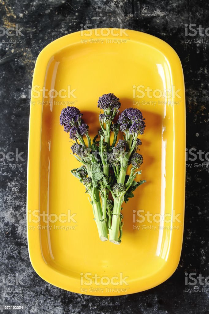 Fresh purple broccoli on a yellow plate. Dark background. stock photo