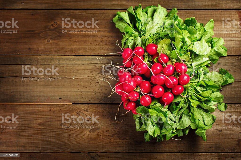 Fresh radish bunch on rustic wooden background stock photo