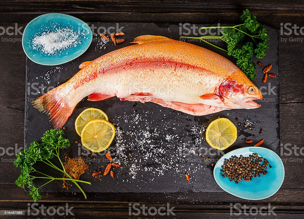 fresh rainbow trout fish with spices on dark wooden table stock photo