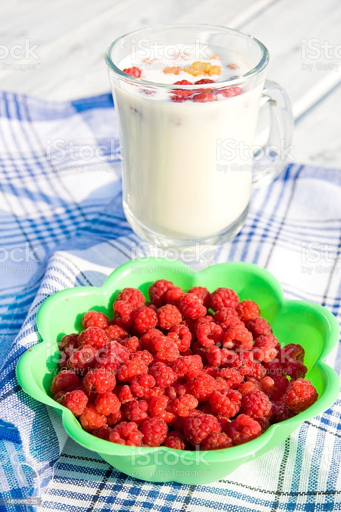 Fresh raspberry and cup of milk on wooden rustic desk royalty-free stock photo