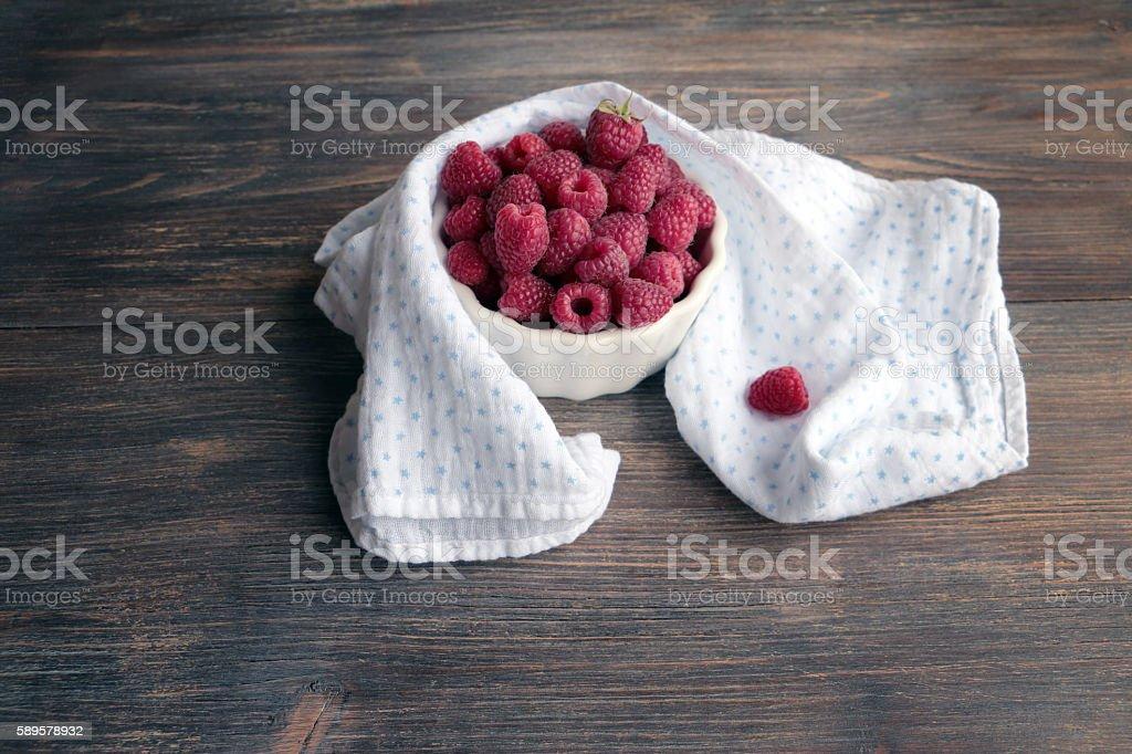 Fresh raspberry in bowl with cotton napkin stock photo