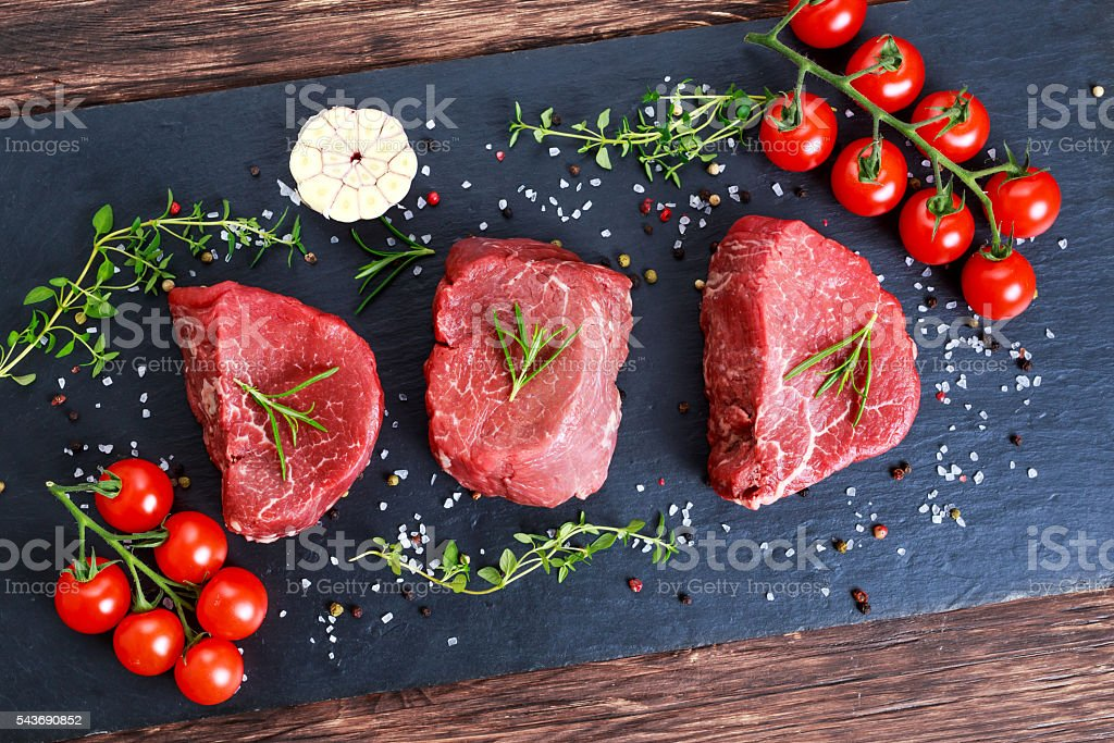 Fresh Raw Beef steak Mignon, with salt, peppercorns, thyme, garlic. stock photo