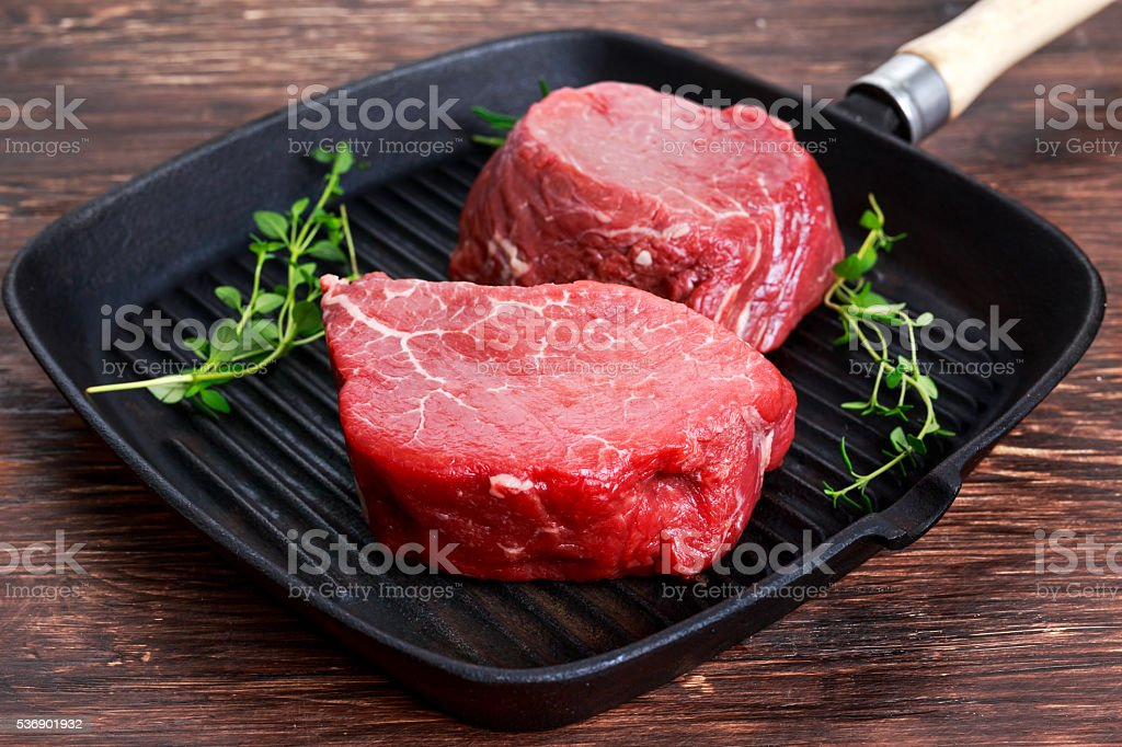 Fresh Raw Beef steak Mignon with thyme on grilled pan stock photo