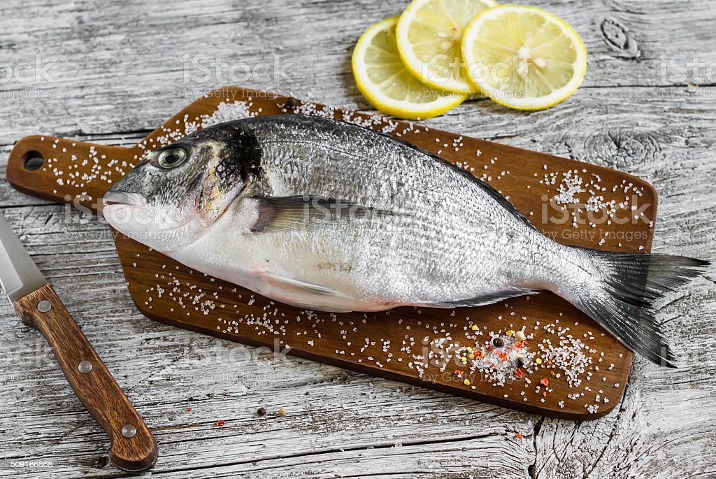 Fresh raw Dorado fish on wooden rustic background stock photo