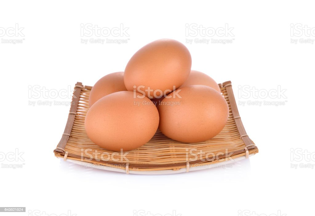 fresh raw eggs in bamboo basket and on white background stock photo