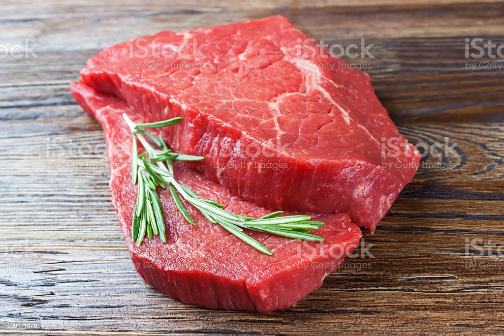 Fresh raw meat with rosemary stock photo