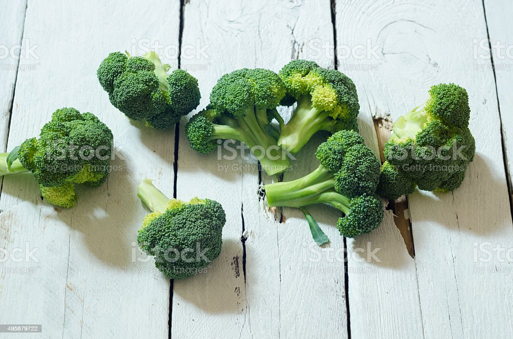 Fresh raw organic broccoli on wooden white background stock photo
