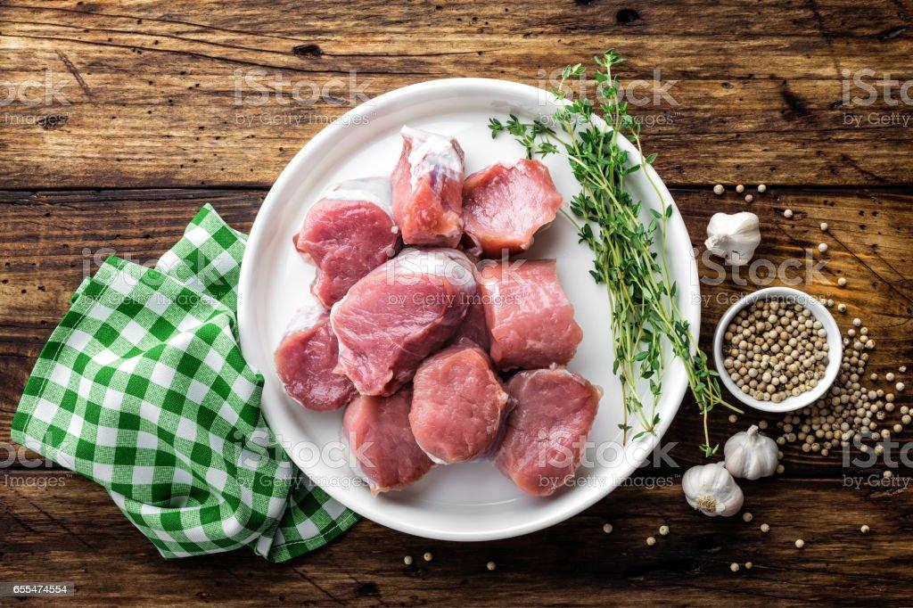 Fresh raw pork tenderloin, chopped meat on dark wooden rustic background, top view stock photo