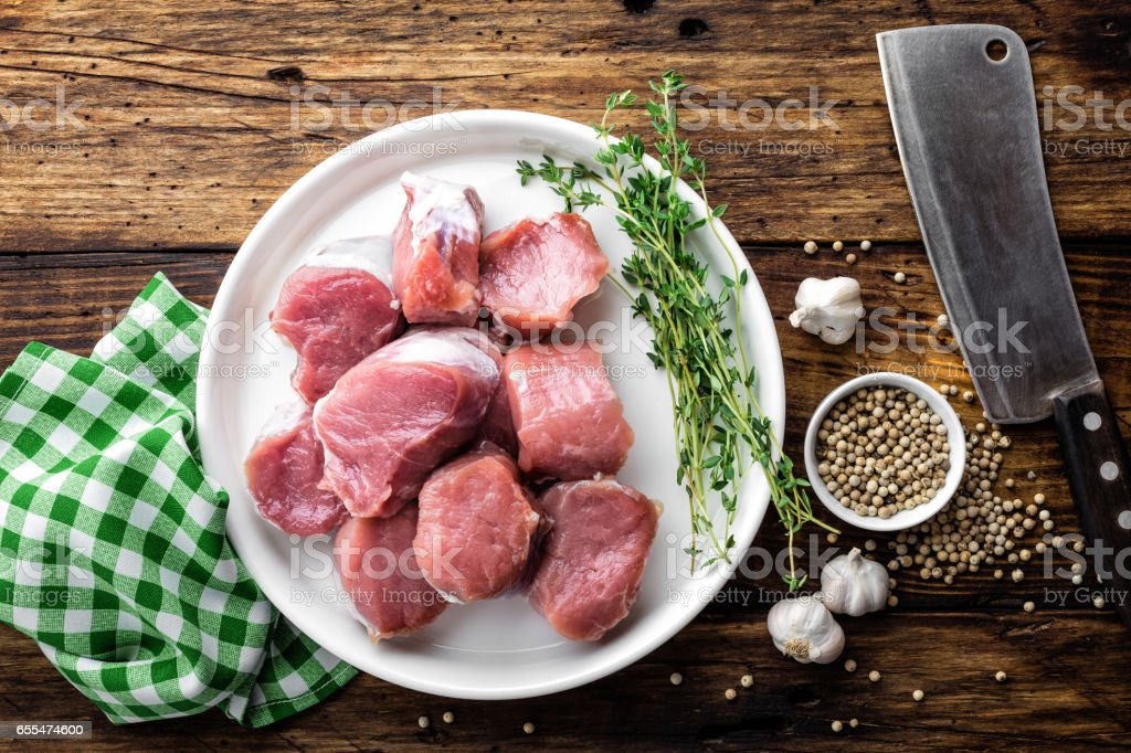 Fresh raw pork tenderloin, chopped meat on dark wooden rustic background, top view stock photo