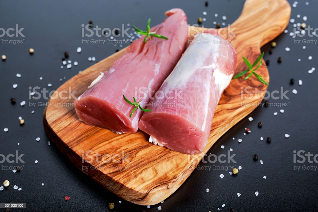 Fresh Raw pork tenderloin on wooden board .ready to cook stock photo