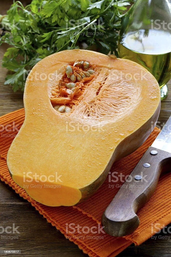 fresh raw pumpkin sliced ​​on a wooden table royalty-free stock photo