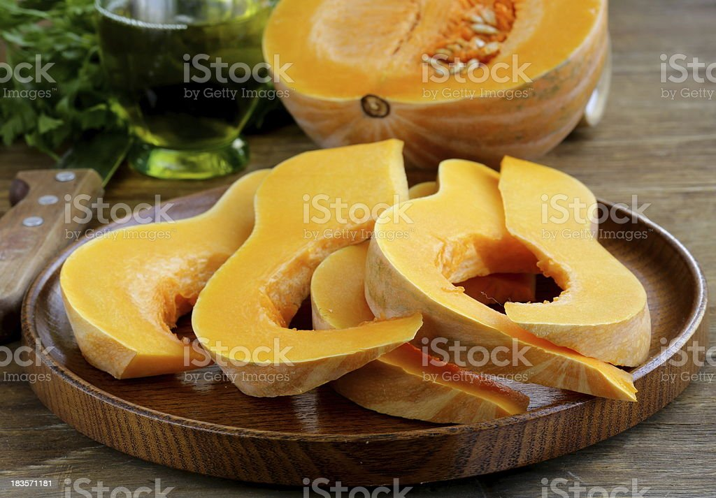 fresh raw pumpkin sliced on a wooden table royalty-free stock photo