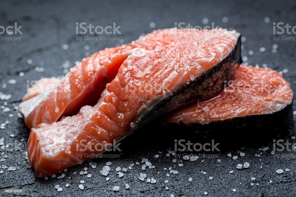 Fresh raw salmon on a black rock royalty-free stock photo