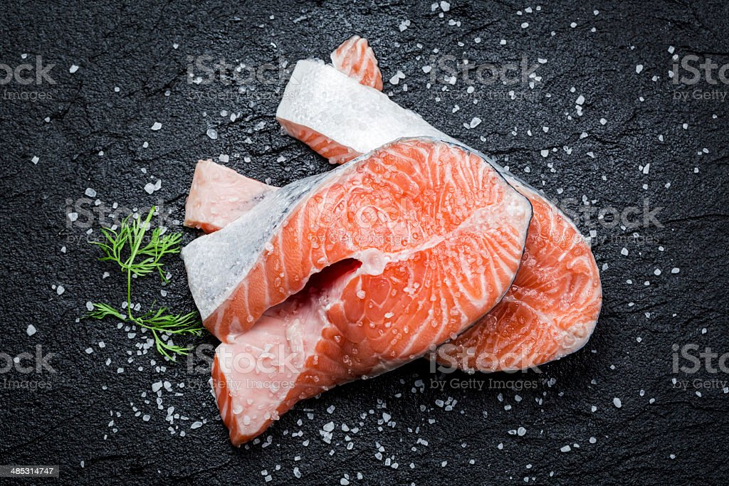 Fresh raw salmon on black rock stock photo