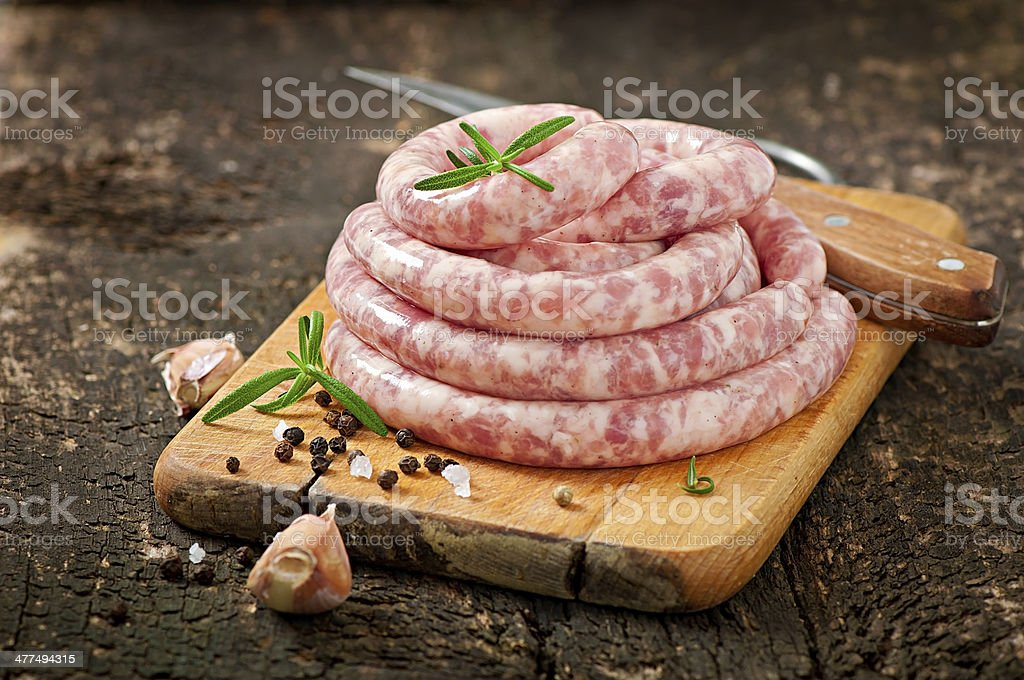 Fresh raw sausage on the old wooden background stock photo