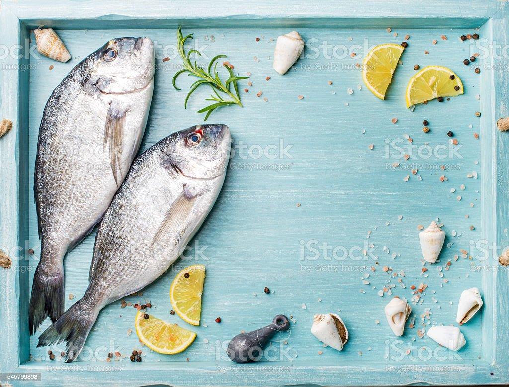 Fresh raw sea bream fish decorated with lemon slices, herbs stock photo