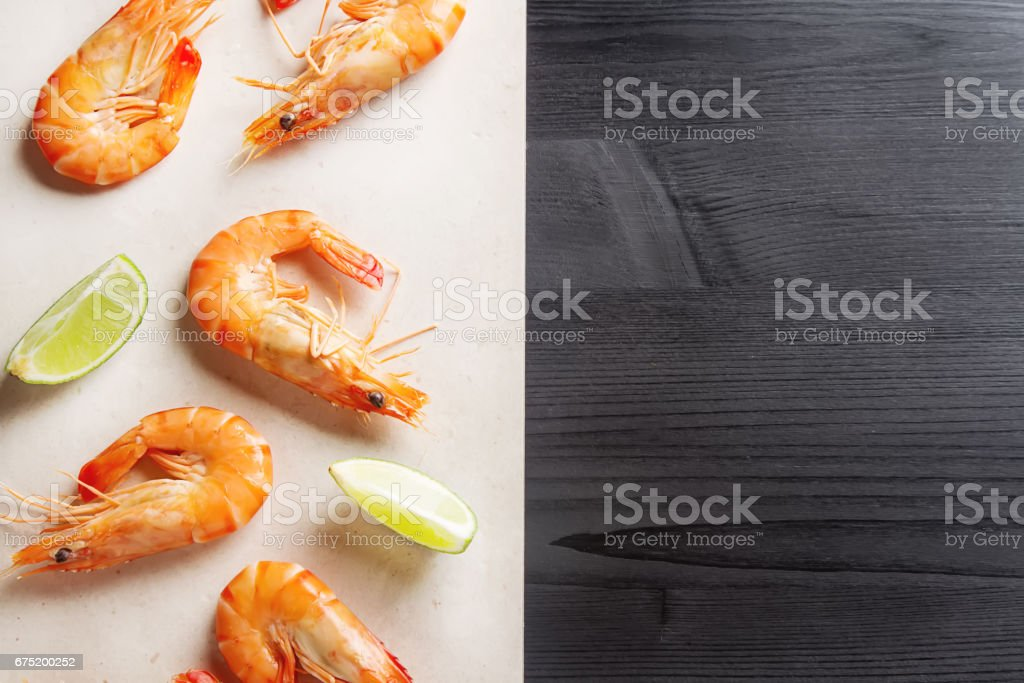 Fresh raw shrimps, lime in a bowl on a wooden table. Eating seafood. Dark background. Top view stock photo