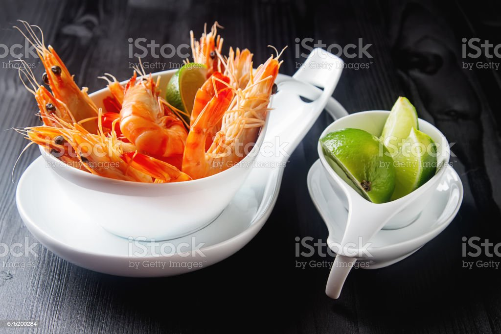 Fresh raw shrimps, lime in a bowl on a wooden table. Eating seafood. Dark background. stock photo