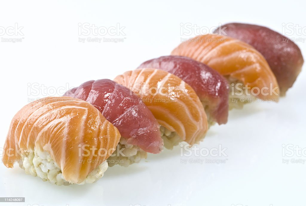 Fresh, Raw Sushi in a Row Against a White Background  stock photo