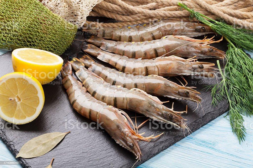 Fresh raw tiger prawns and fishing equipment stock photo