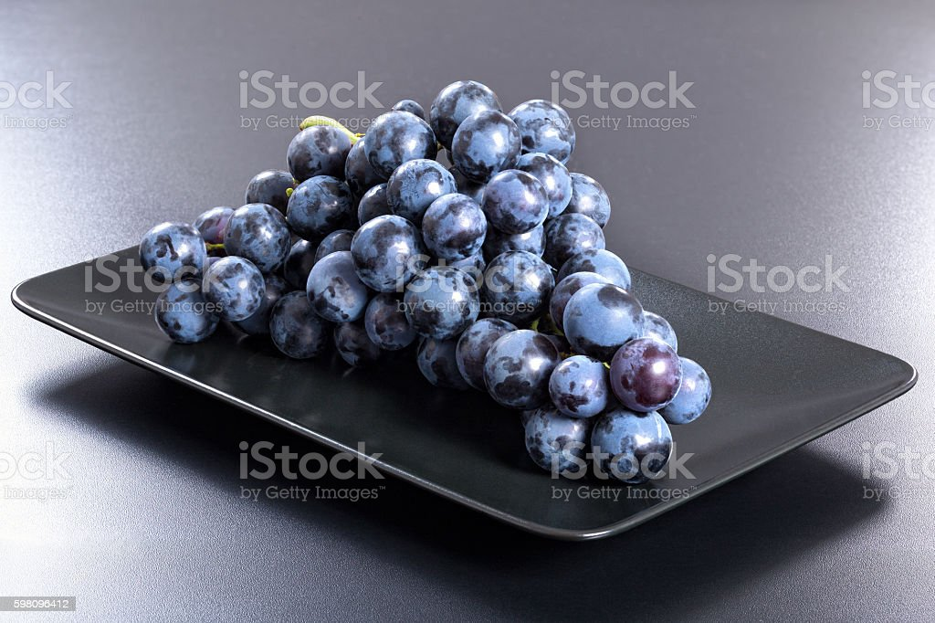 Fresh red grapes bunch on black rectangular dish stock photo